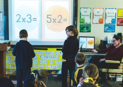 Two children standing in front of the class solving a math problem