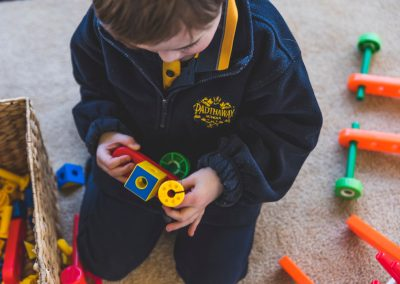 Child playing lego with school's jumper on